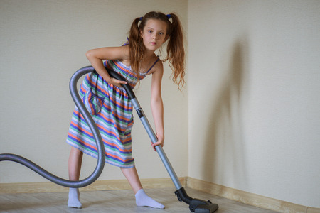 vac: Little beautiful girl running with vacuum cleaner at home.