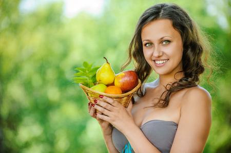 beautifu: Portrait of beautifu young woman holding a basket of fruit at summer green park