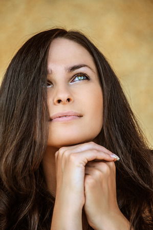 Portrait of young charming cheerful woman propping up her face against beige background. photo