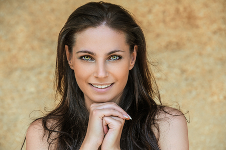 provocative woman: Portrait of young charming cheerful woman propping up her face against beige background.