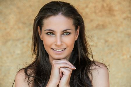 Portret van jonge charmante vrolijke vrouw stutten haar gezicht tegen de beige achtergrond.