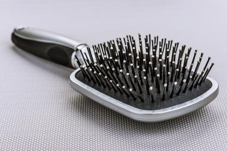 plastic comb: Massage black comb lying on gray napkin.