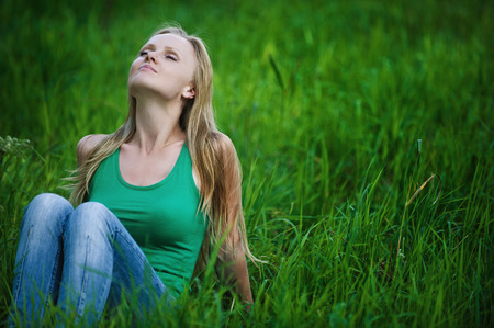 Portrait of beautiful young woman eyes closed sits on green grass at summer green park photo