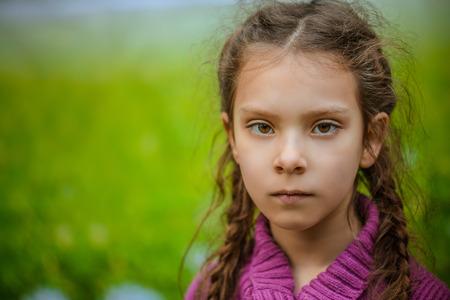 fille triste: portrait de jeune fille mignonne dans la robe, sur le fond du parc verdoyant d'été