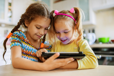 family together: Two beautiful little sisters sit at a table and play on a Tablet PC.