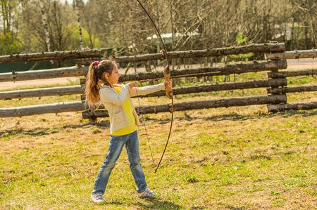 pointed arrows: Beautiful little girl shoots bow at entertainment park.