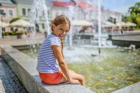 water flowing: Little girl holds legs over fountain and laughs.