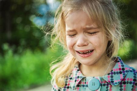 beautiful sad: Beautiful sad little girl crying, on summer background. Stock Photo