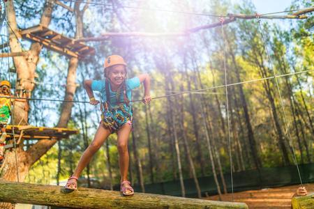 Meisje klimmen in de adventure park is een plek waar een breed scala van elementen, zoals touw klimmen oefeningen, hindernisbanen en zip-lijnen kunnen bevatten.