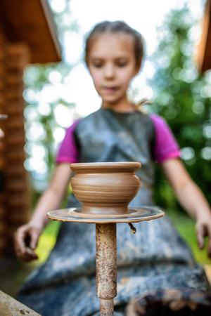 potters wheel: Little girl produced on potters wheel pot. Stock Photo