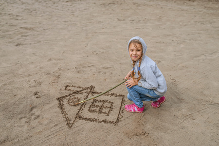 children drawing: Little beautiful girl in hood draws in sand image of house. Stock Photo