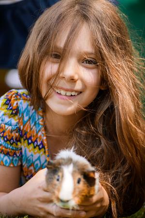 girl lying: Little girl lying on grass and petting guinea pig.