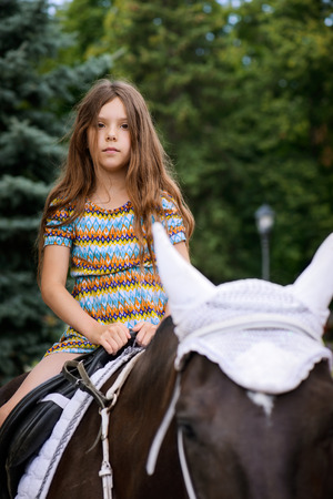 Little girl riding festive horse in summer city Park. Stock Photo