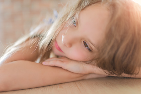 irritable: Little pretty thoughtful girl sitting on the brick wall background.