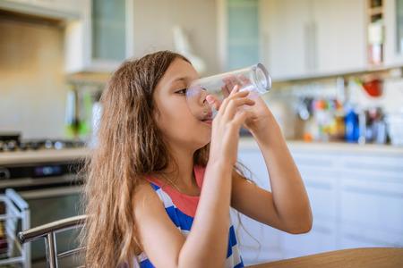 Kleine schöne Mädchen glücklich trinkt ein Glas Wasser in der Küche. Standard-Bild - 46740585