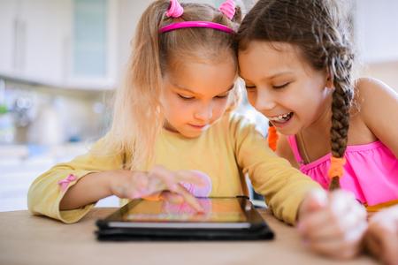 Twee mooie kleine zusjes zitten aan een tafel en spelen op een Tablet PC. Stockfoto