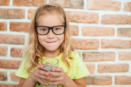 drink water: Beautiful smiling little girl drinks water on a background of a brick wall. Stock Photo