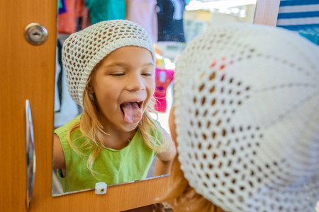 declare: Beautiful smiling little girl looks in the mirror and shows tongue. Stock Photo