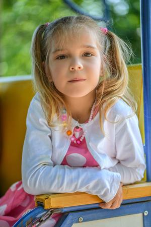 petite fille triste: Belle petite fille triste avec des nattes assis sur une chaise dans un parc verdoyant de l'été.