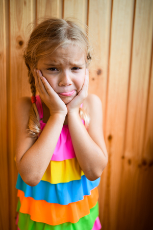 only girls: Beautiful sad little girl on the background of wooden wall. Stock Photo