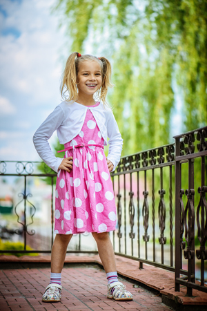 little girl dress: Beautiful smiling little girl in a pink dress standing near the fence.
