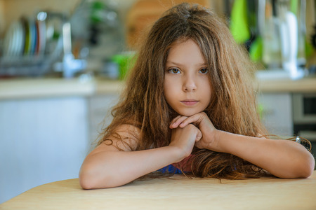 Little pretty thoughtful girl on the background of the kitchen. Stock Photo