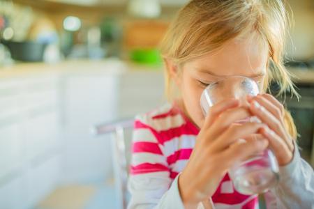 tomando agua: Hermosa niña sonriente beber un vaso de agua contra el fondo de la cocina.