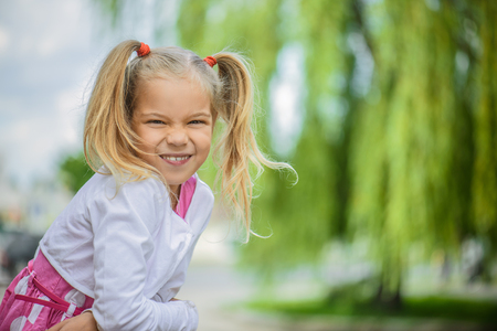 small girl: Beautiful smiling little girl in a pink dress on a background of green summer city park. Stock Photo
