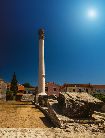 metres: In very centre of Nin, Croatia, on location of once Roman forum, remains of monumental Roman Temple can be found. On Temple there was a Corinthian column which had an original height of 17 metres. Stock Photo
