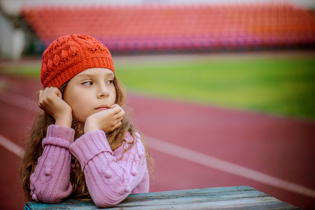 frenchwoman: Little beautiful girl in a red cap and pink sweater has reflected on the background of a large stadium.