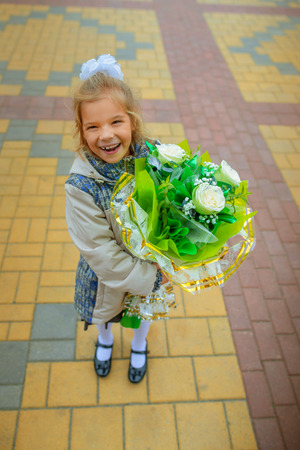 first day: Little beautiful happy girl goes to school with a bunch of flowers.