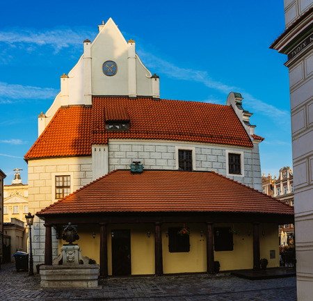 pitched roof: Weight town and Manhole Bamberg in Poznan - story building in the Old Market in Poznan, very high, pitched roof and simple tops of shared pilaster strips located at western wall of Town Hall, Poland.
