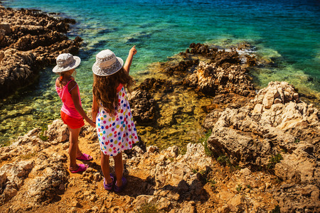 woman beach dress: Two beautiful little sisters on the rocky shores of the Adriatic Sea in Croatia. Stock Photo