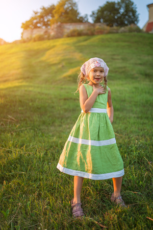 nature green: Beautiful little girl in a green dress on a background of summer city park. Stock Photo