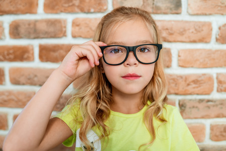 glass brick: Beautiful smart little girl in glasses with black frames on the brick wall background.