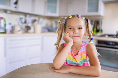 young schoolgirl: Beautiful little girl sitting at table and smiling. Stock Photo