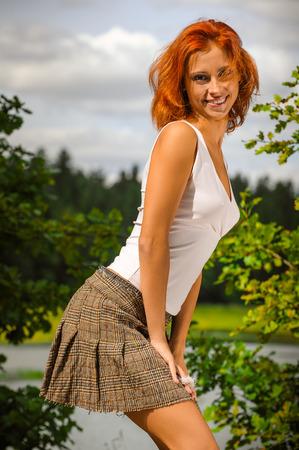 ojos verdes: Mujer hermosa zanahoria de pie cerca de un lago, en el verde parque de verano.