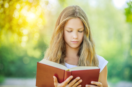 pretty young girl: Beautiful teenage girl reading red book, against green of summer park.
