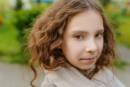 Beautiful little girl with long wavy hair close-up on background of spring city park. photo
