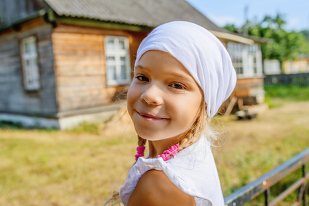 Little beautiful calm girl in a white scarf against background of rural house. photo