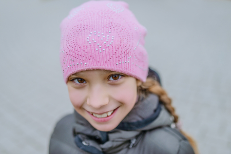 Beautiful little girl in pink hat and gray jacket. photo