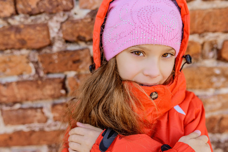 Portrait of beautiful little girl in pink hat and jacket on red background of wall.