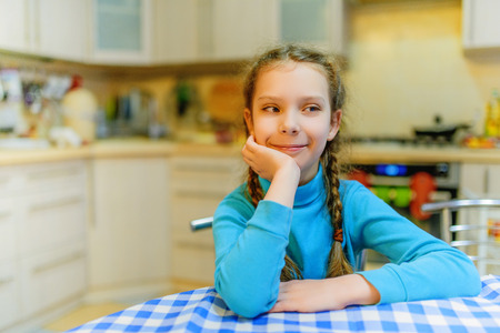 Little pretty smiling girl on background of kitchen. photo