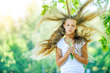 Portrait of beautiful teenage wind with flying hair, against green of summer park. Stock Photo
