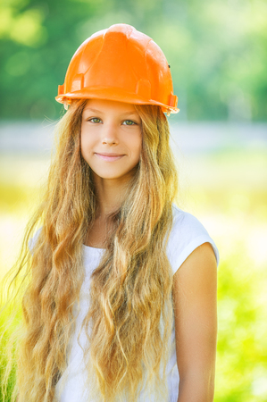 Portrait of beautiful teenage girl in an orange helmet, against green of summer park. photo