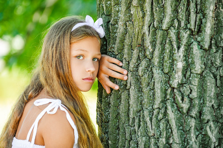 Young beautiful girl near large tree, against green summer garden. photo