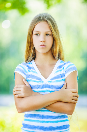 Beautiful sad teenage girl in blue blouse, against green of summer park. photo