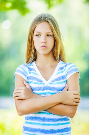 Mooi triest tiener in blauwe blouse, tegen groen van de zomer park.