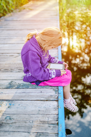 Little beautiful girl sitting on a river pier, and read e-books. photo
