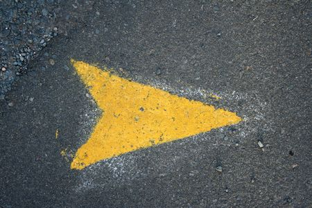 Yellow arrow pointing right painted onto an asphalt road   photo